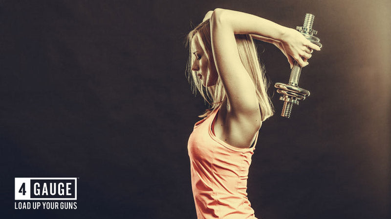 Athletic blonde-haired woman in activewear doing a triceps extension with a light dumbbell