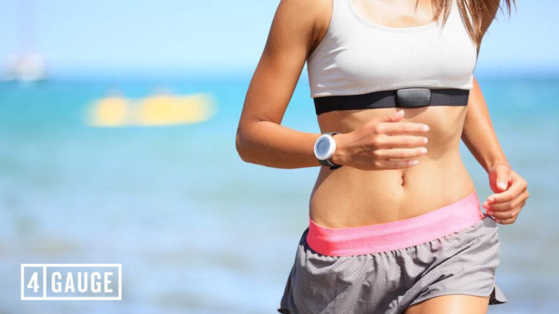 Young, athletic woman running on a beach wearing a heart rate monitor