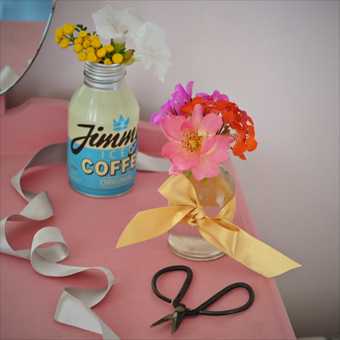 Glass bottle of flowers with a ribbon tied around it
