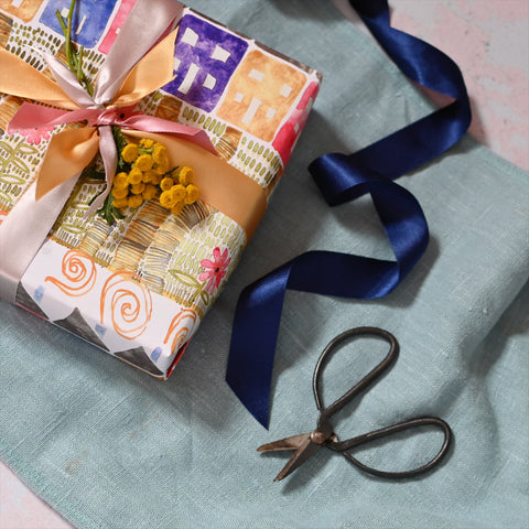 Gift wrapped with mi casa wrapping paper and multiple ribbons