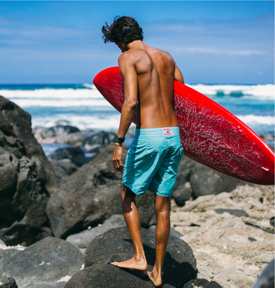 Man standing on rocks holding surf board and wearing Birdwell 311 board shorts