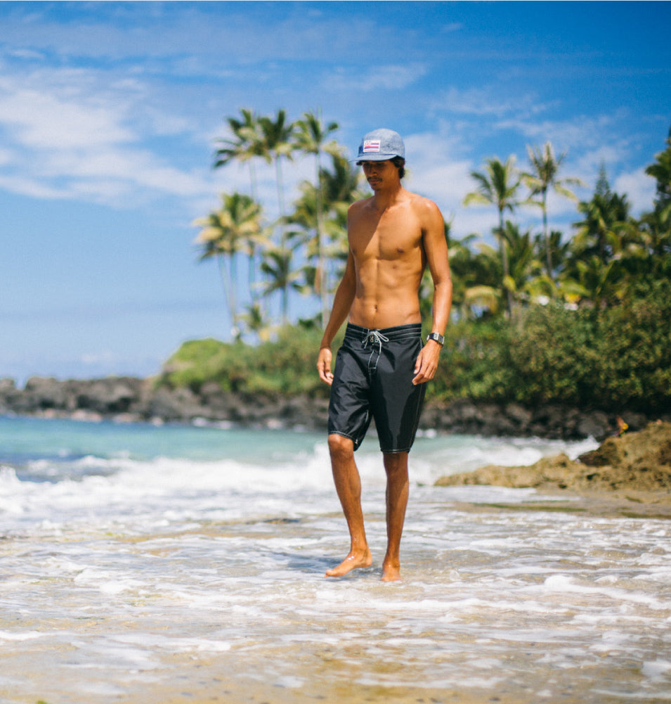 Man wearing long 312 Birdwell Board shorts standing on beach