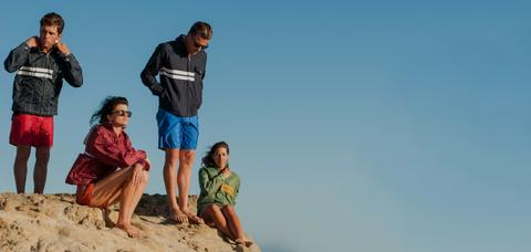 Four persons on a rock wearing Birdwell jackets and Birdwell board shorts