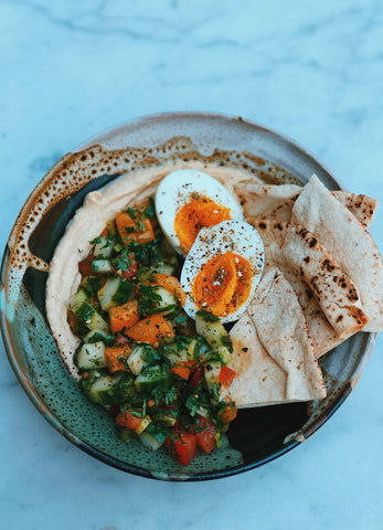 Chopped salad with cucumber, tomato, hummus, pita and soft boiled eggs