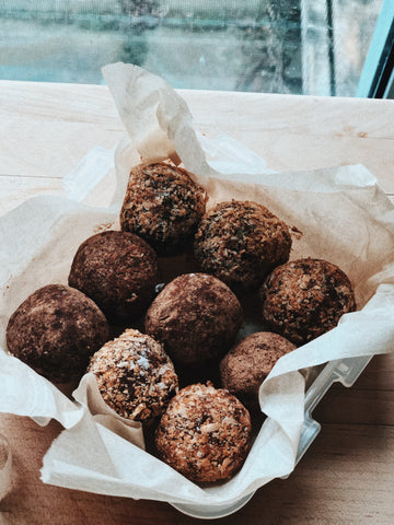 date and tahini energy balls in a baking tray with wax paper