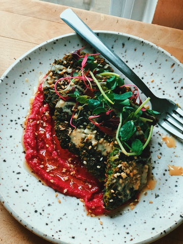 herby green falafels on a bed of beetroot hummus with sprouts on top