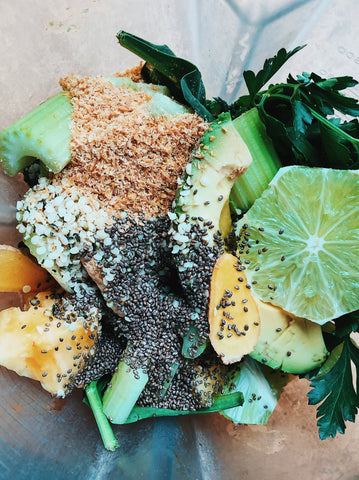 Ingredients for green smoothie all tossed into a blender: handfuls of spinach, parsley, ginger, lime, pineapple, avocado, stalks of celery, flax seed and chia seed.