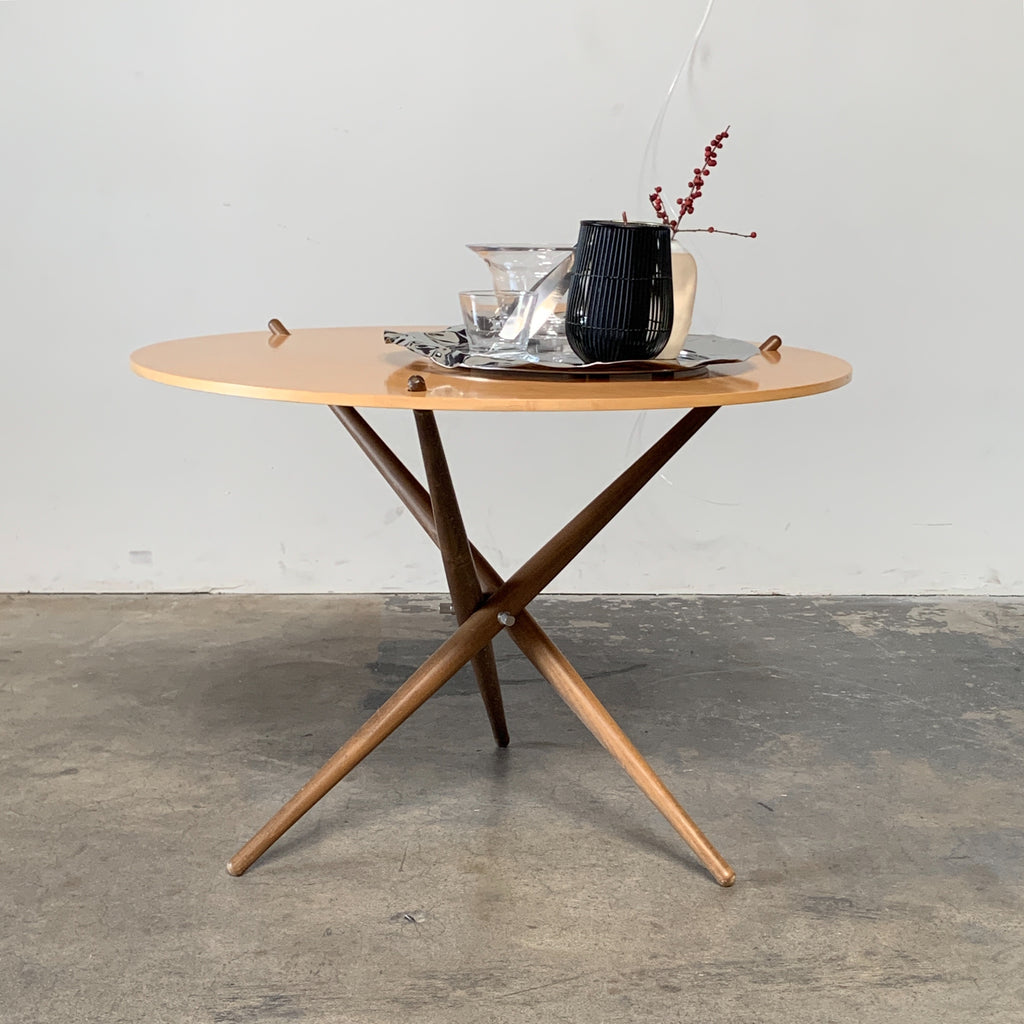 Knoll 'Folding Tripod Table' by Hans Bellmann Light wood top with darker wood base. Shown with stainless steel tray from Alessi. For sale at Modern Resale in Los Angeles