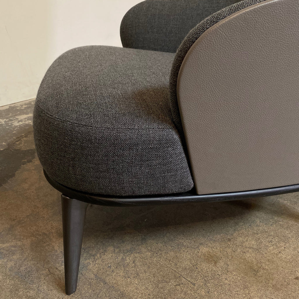 Detail Shot - Minotti 'Leslie' Armchair & Ottoman  The Minotti 'Leslie' chair and ottoman is sensuous with soft contours and rich materials. Textured gray fabric is backed by smooth, hard taupe colored leather. An ebony stained wood base defines and compliments.   Los Angeles