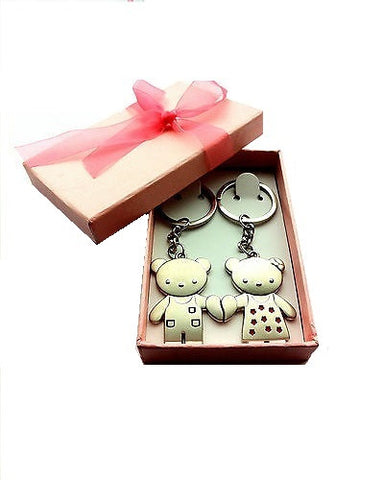 Image of 2 small bear key-rings holding hands inside a stylish box.