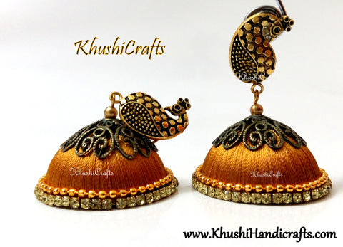 Gold Designer Extra large Silk Jhumkas enhanced with a Peacock Stud