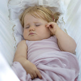 sleeping outside in her dusty rose organic merino vest and swaddle blanket from roots & wings organic merino