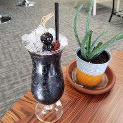 Zombie Apocalypse cocktail on indoor table with plant