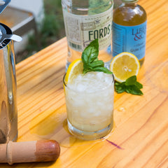 Gin Basil Smash cocktail on outdoor bar with bar tools and bottles
