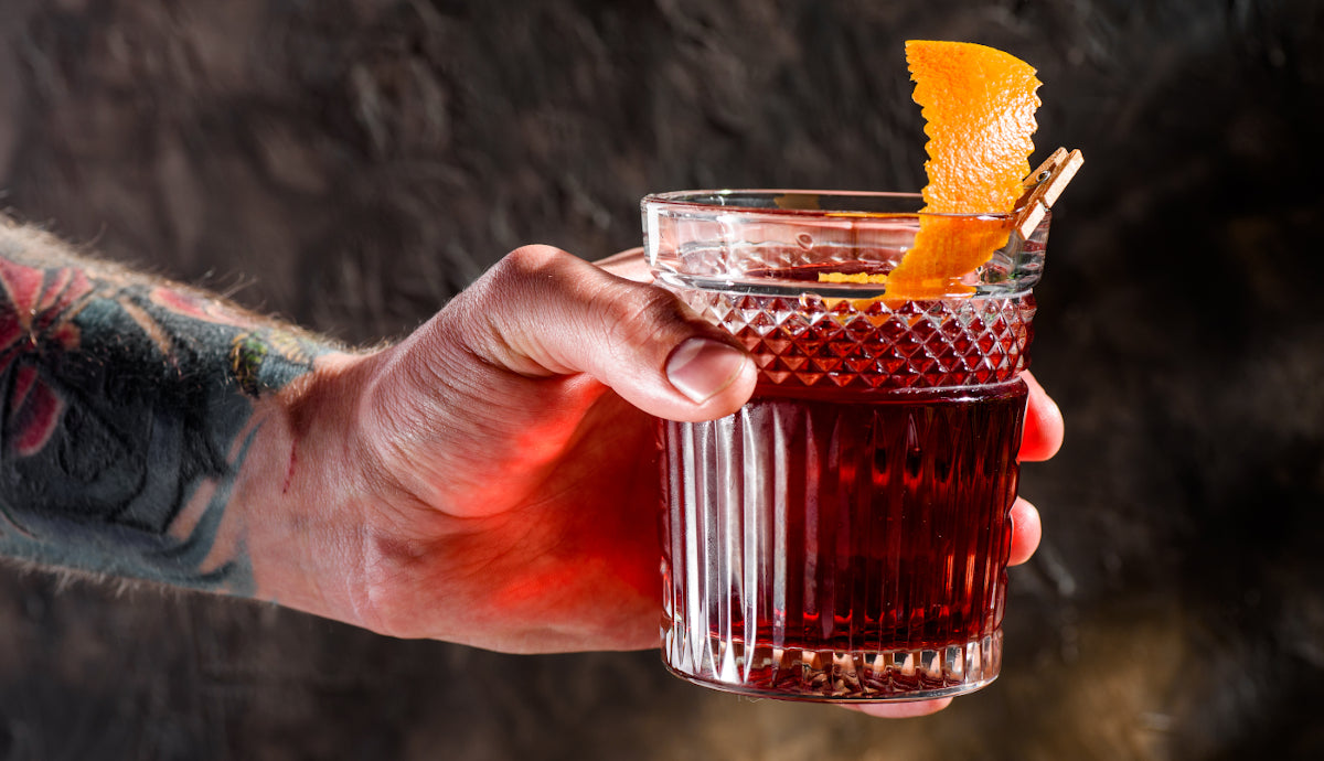 Tattooed bartender hands over the negroni