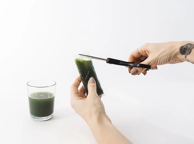 Wheatgrass juice package being cut with scissors