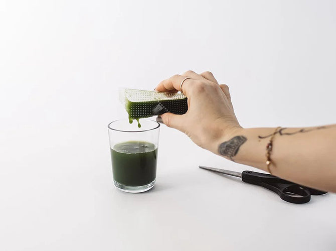 Wheatgrass juice being poured into a glass