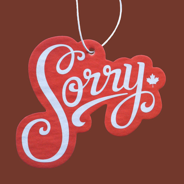 Hand-lettered Sorry peppermint scented car air freshener, red with white type.