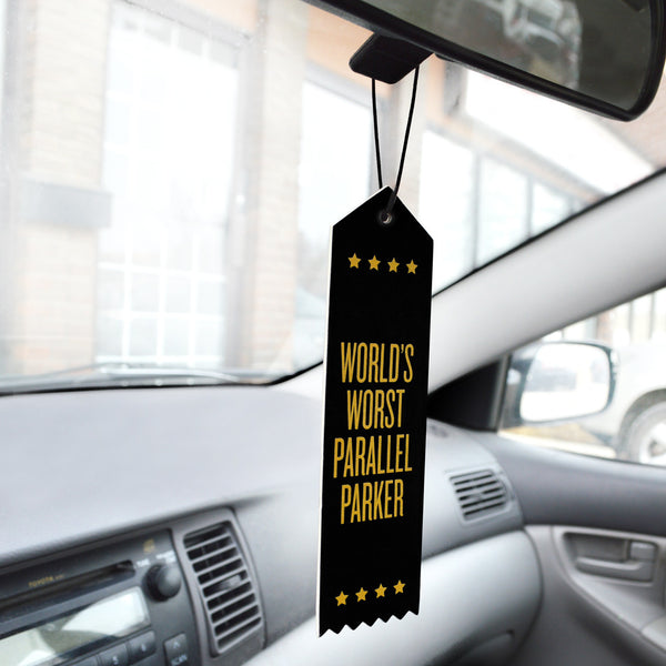 Worlds Worst Parallel Parker coffee scented car freshener, black with gold colored type in shape of ribbon award