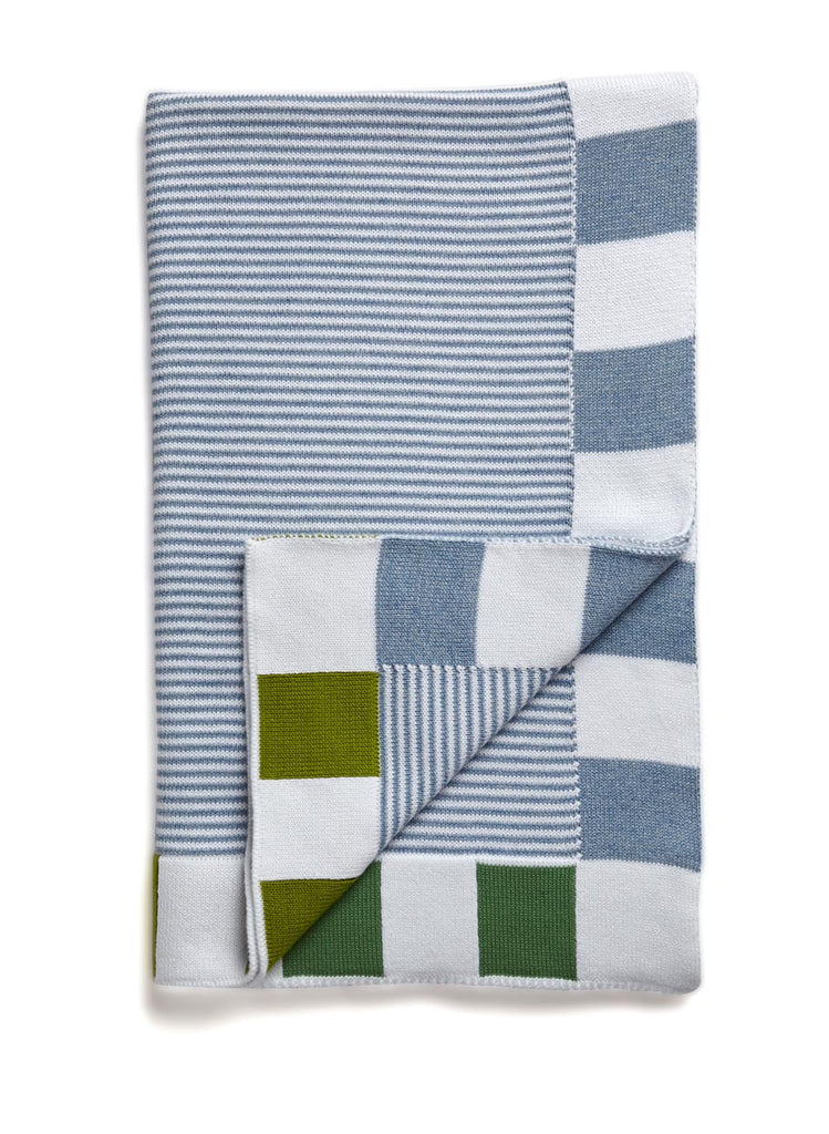 A striped baby blanket in classic washed denim colour.  The thin stripes contrast against a bold block trim of blue and green.