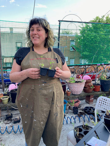 Ruby stands on a concrete patio wearing a paint-stained split leg apron, holding a small seedling that will be planted in one of the containers behind her.