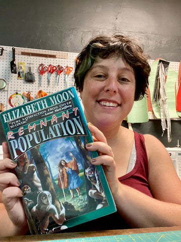 Ruby sits at the table in her sewing studio holding up a hardcover book titled Remnant Population. The book cover depicts an old woman in an orange cape standing at the edge of a forest, with owl-like creatures inside the forest looking back at her.