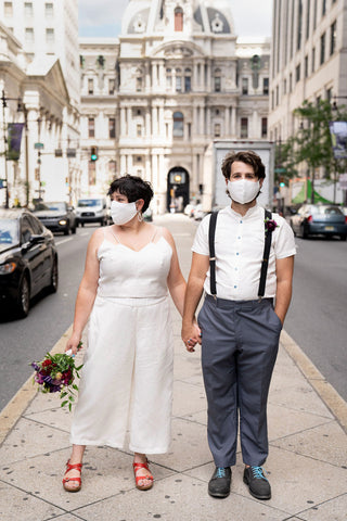 Two people stand in front of City Hall in Philadelphia wearing wedding clothes and matching white face masks.