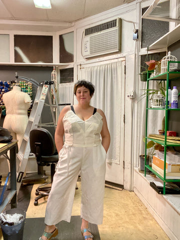 Ruby stands in her studio wearing a muslin mock-up of her wedding clothes.