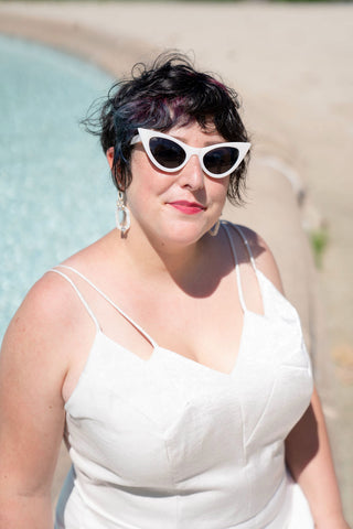 Ruby is pictured from the waist up sitting on the ledge of an outdoor fountain. She is wearing her handmade wedding clothes and white plastic cat eye sunglasses.