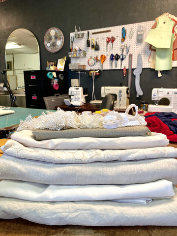 Several cuts of white fabrics lay stacked on a cutting table in a sewing studio.