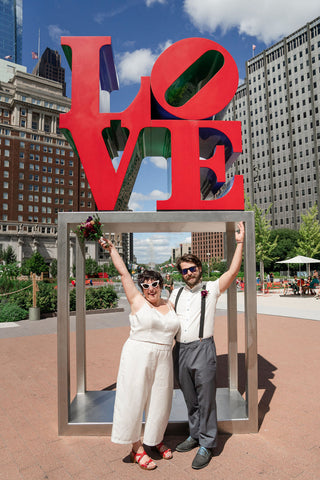 Two people stand in front of the LOVE sculpture in Philadelphia in wedding clothes. They are smiling and sticking out their arms to frame the sculpture.