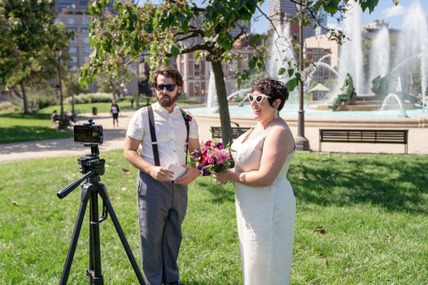 Two people in wedding attire stand in front of an outdoor fountain, looking at a camera mounted on a tripod.