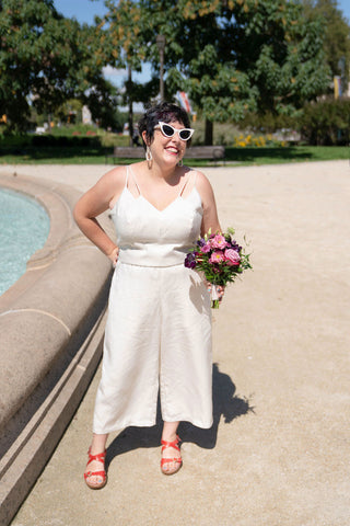 Ruby stands next to an outdoor fountain wearing a white bodice and pants with white cat-eye sunglasses and red sandals. She is holding a bouquet of flowers in one hand.