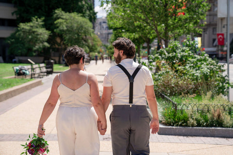 Two people in wedding attire are shown from the back, walking away from the camera.