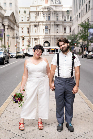 A couple stands in front of city hall in Philadelphia wearing wedding attire. They are holding hands and smiling.