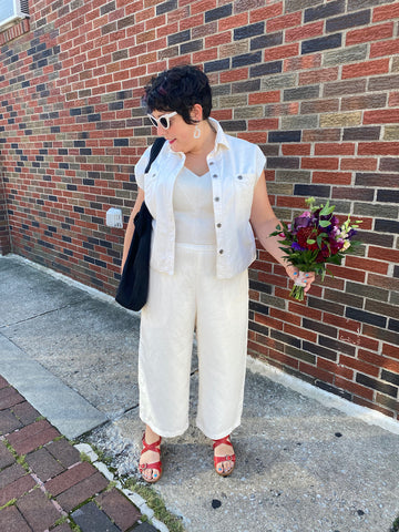 Ruby stands in front of a brick wall wearing a white sleeveless denim-style jacket over a shiny white bodice and white pants, with red sandals. She is holding a bouquet of flowers in one hand and looking down.