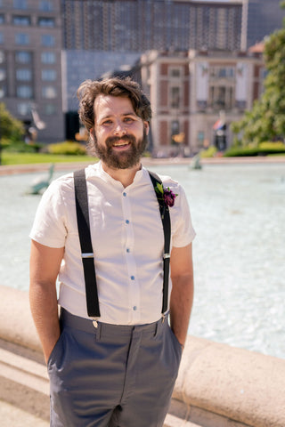 A bearded man in a white short sleeve shirt and suspenders stands in front of a fountain. His hands are in his pockets and he is smiling.