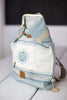 Folded Backpack Beirut Aegean Blue, folded backpack in a multitude of blue toned geometrical patterns and a light blue-jean suede fabric on the back.