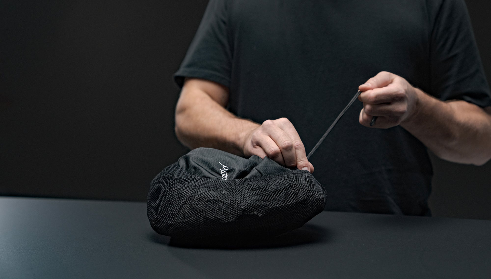 Man cinching down packable pouch