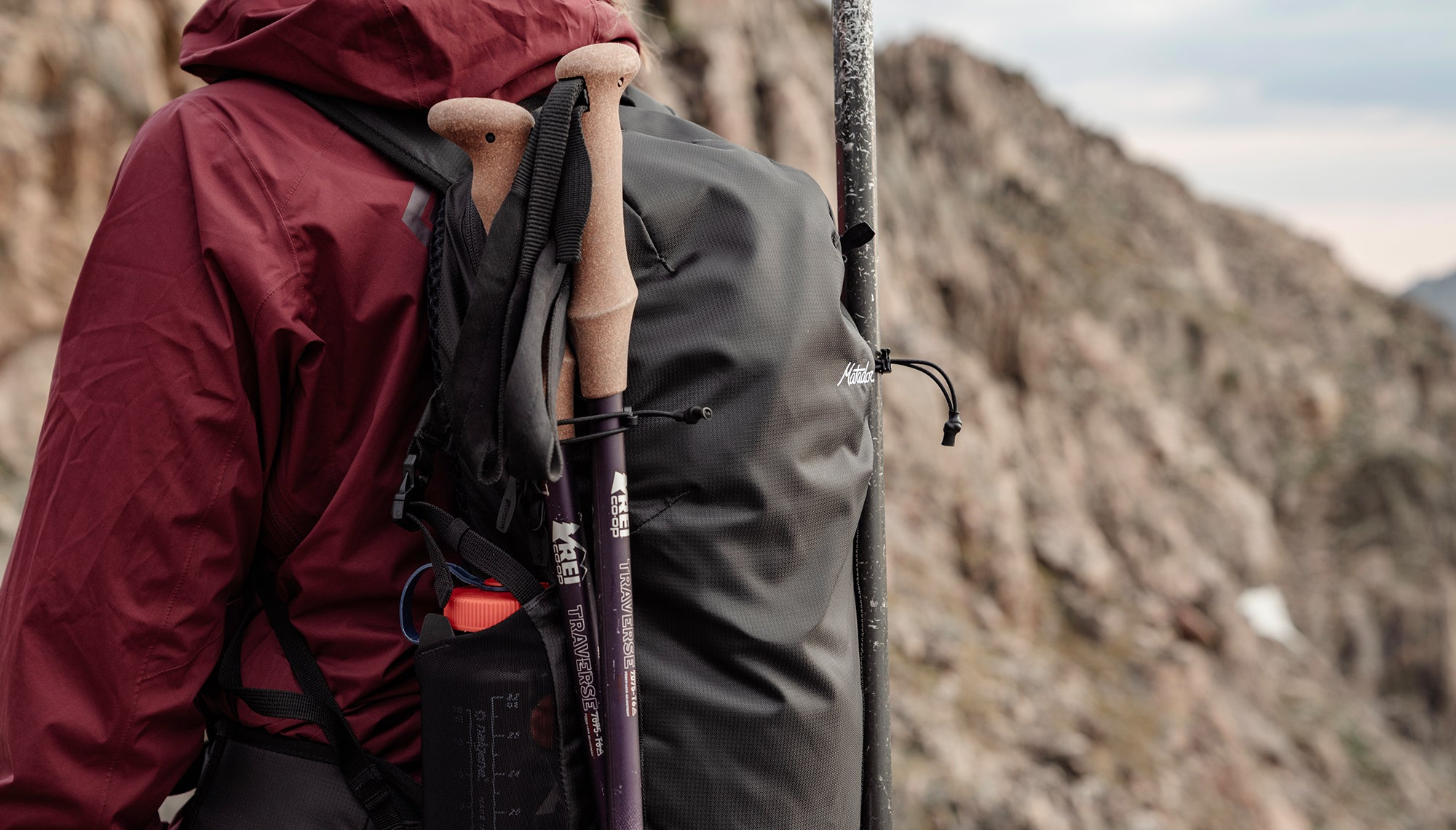 Person wearing a backpack with two trekking poles attached to it