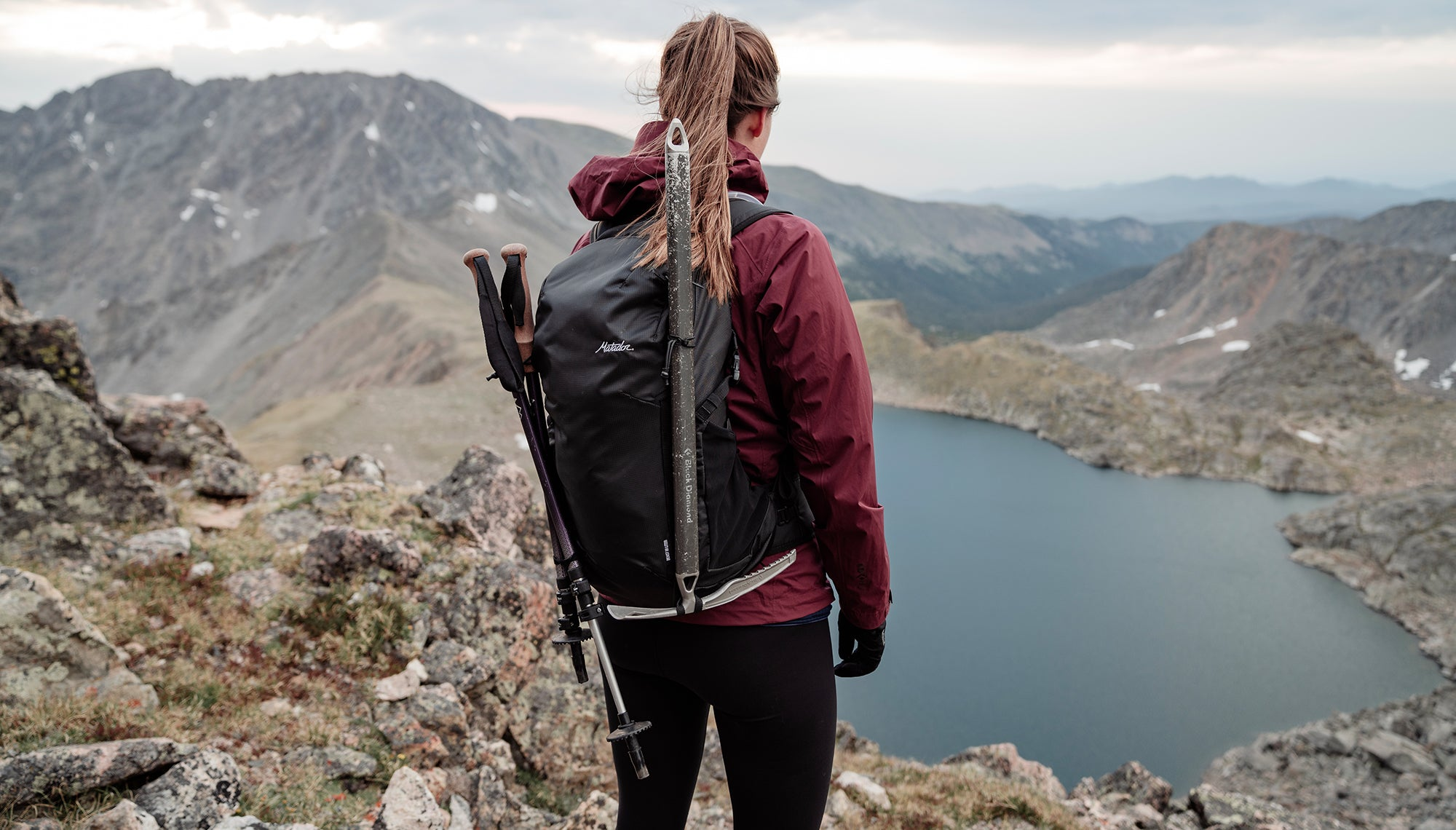 Back view of woman wearing a backpack, standing on a mountain ridge