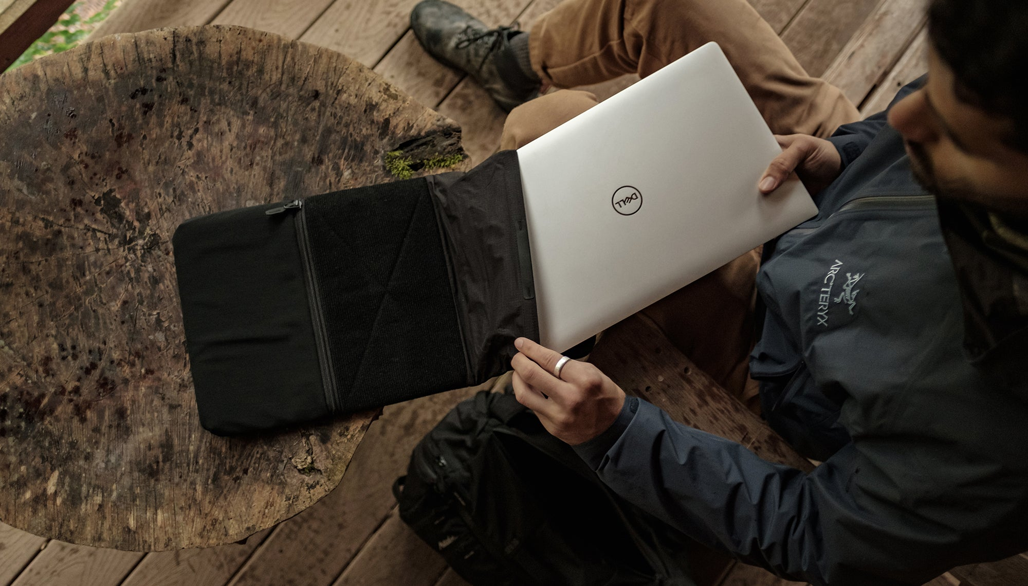 Man in cabin, putting laptop into base layer