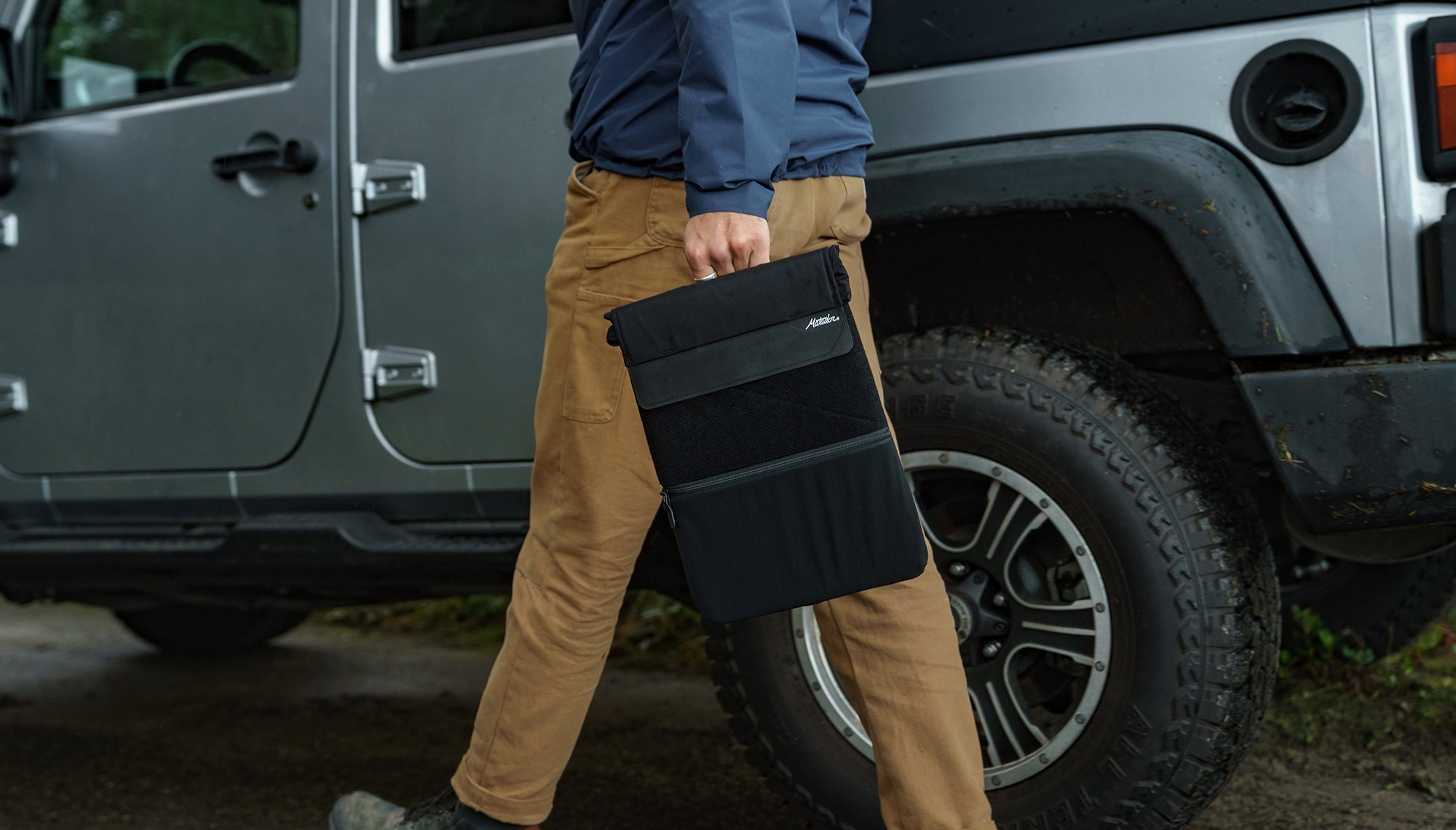 Man walking outside holding laptop base layer by carry handle