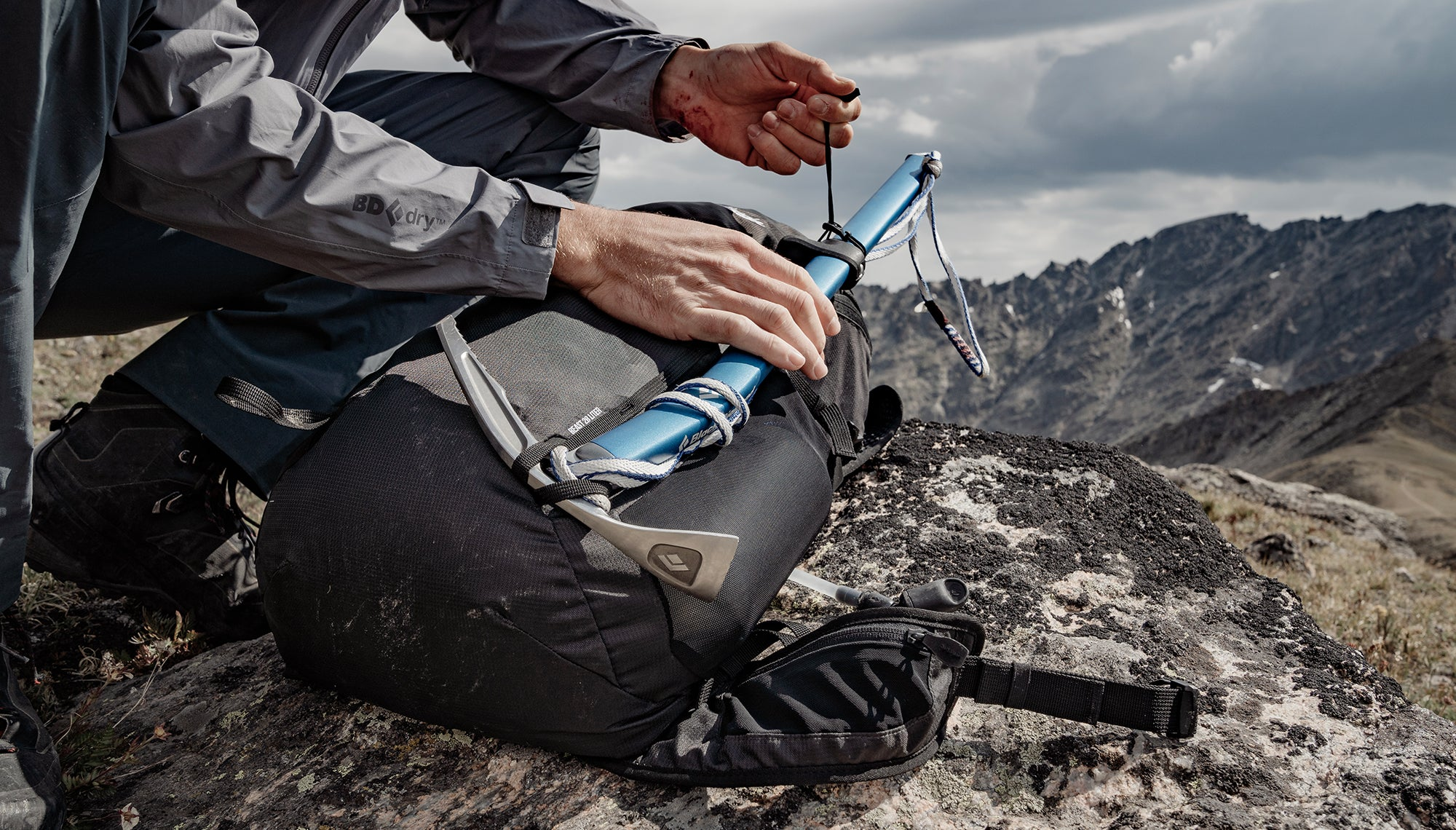 Man attaching ice axe to backpack