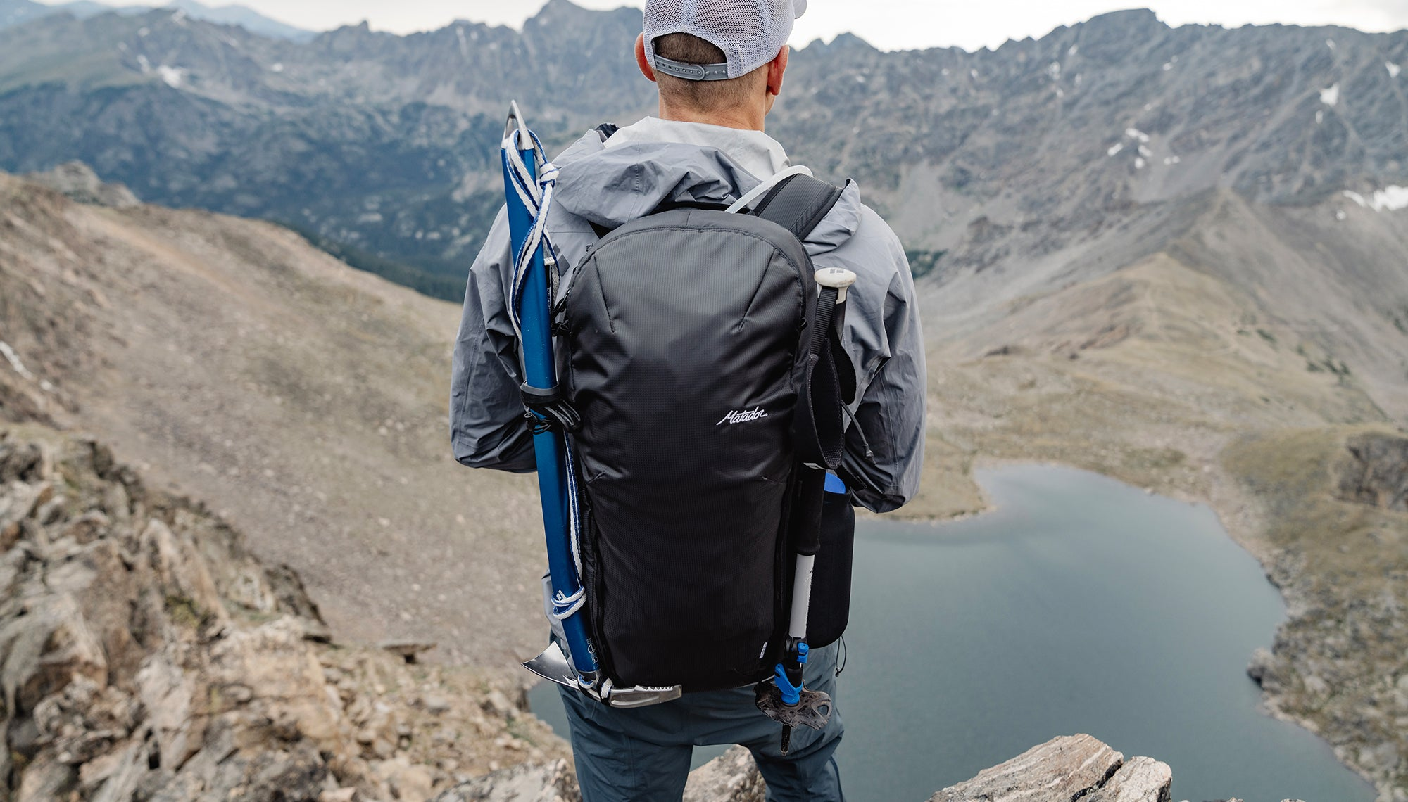 Back view of man wearing a backpack, standing on a mountain ridge