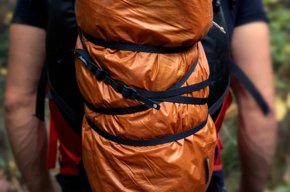 Tether straps wrapped around orange tarp and backpack