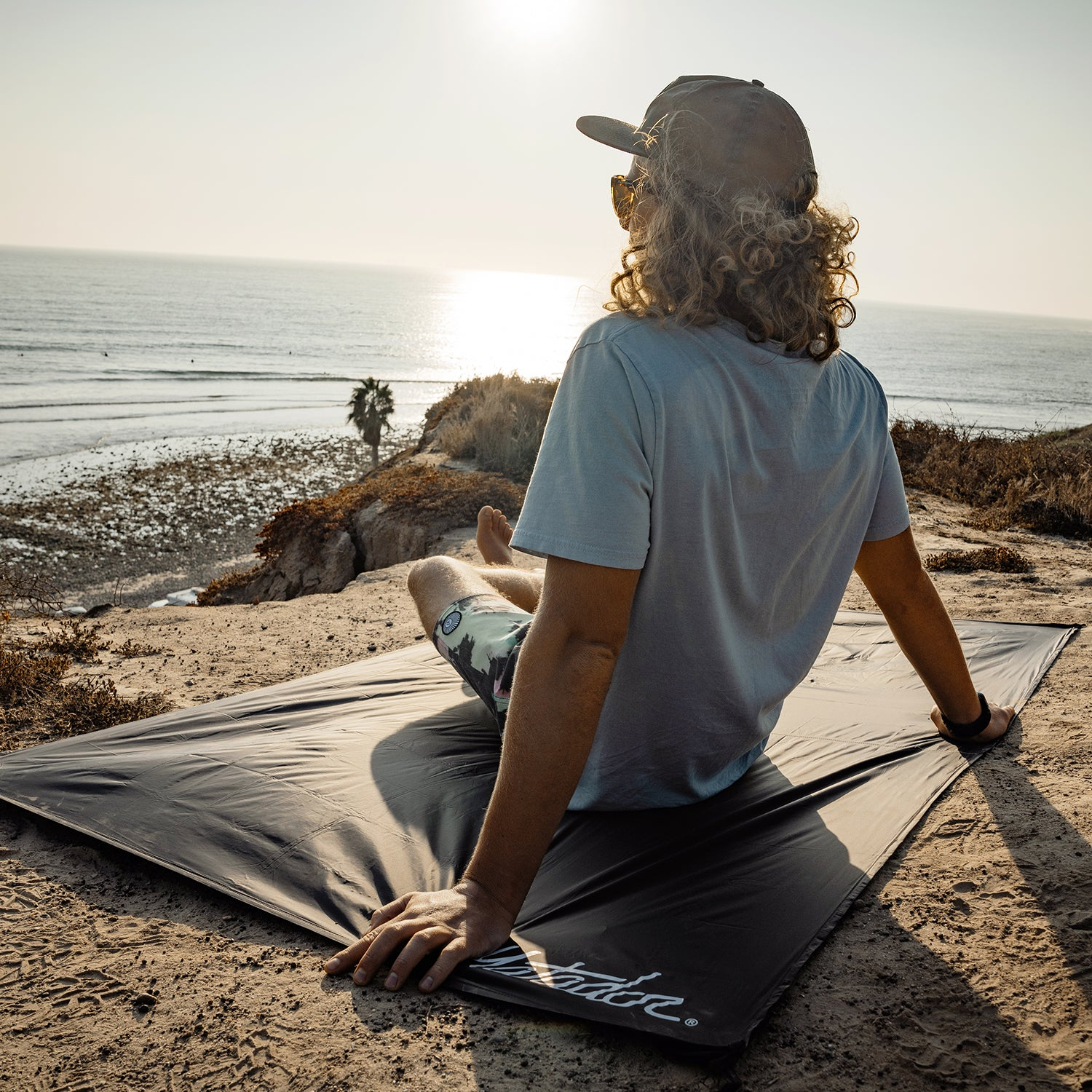 Man looking out to ocean sunset, sitting on a pocket blanket