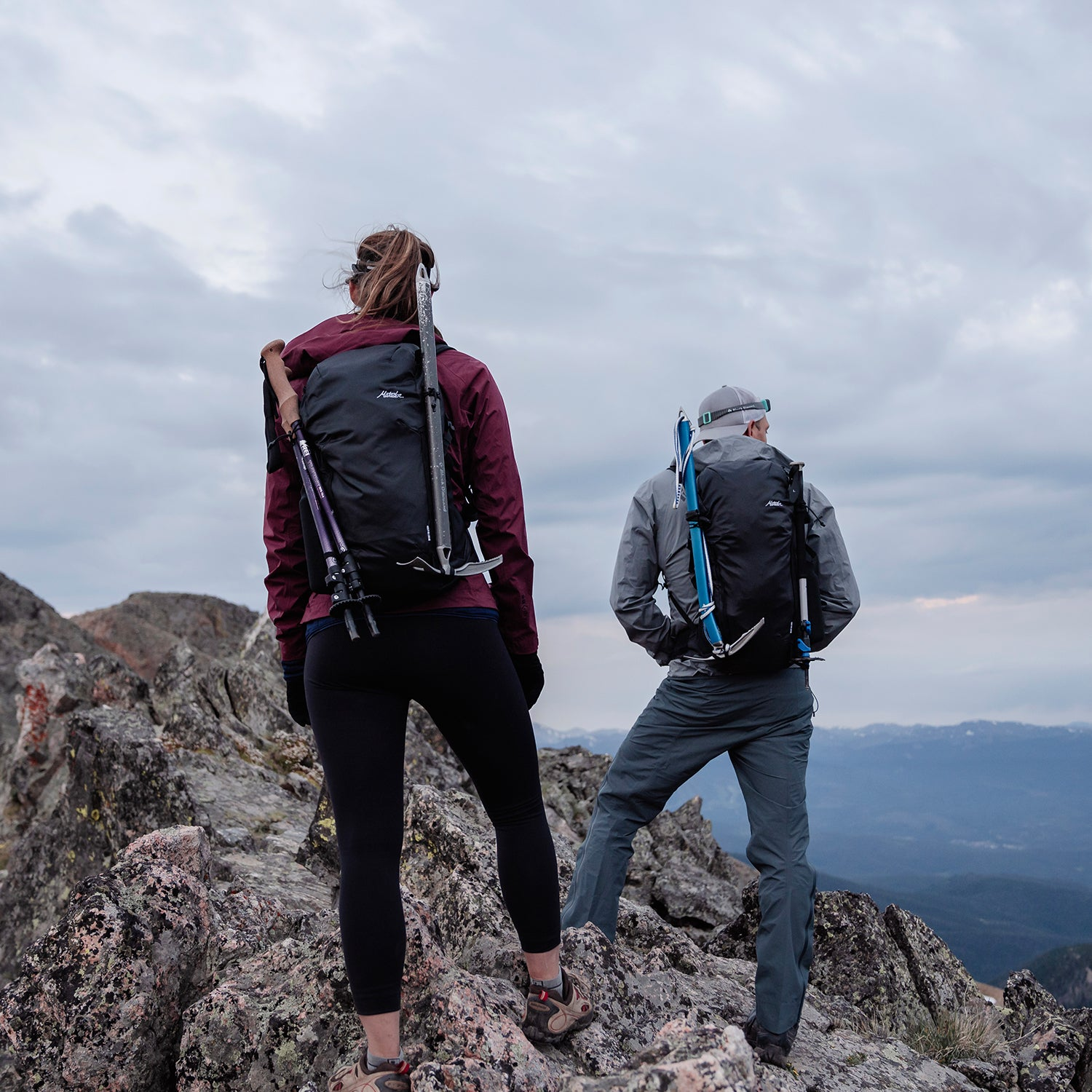 Man and woman standing on top of rocky peak