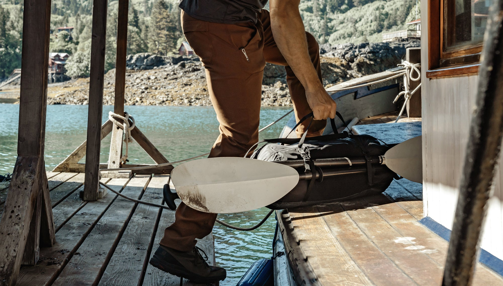 Man carrying duffle with kayak paddles attached