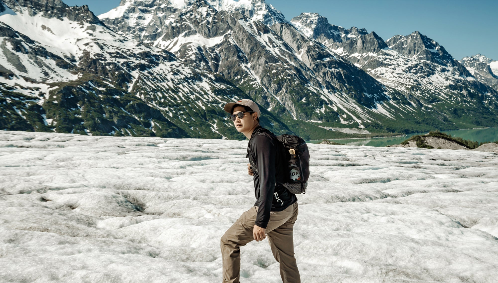 Man standing on glacier in front of snowy mountains